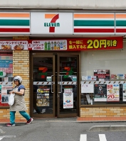 A woman exits a 7-Eleven convenience store, while a man sits in front of a store in Kawasaki City, Kanagawa Prefecture, Japan, on Tuesday, May28, 2013. Photographer: Akio Kon/ Bloomberg